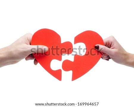 Male and female hand matching red jigsaw heart halves over white background - stock photo