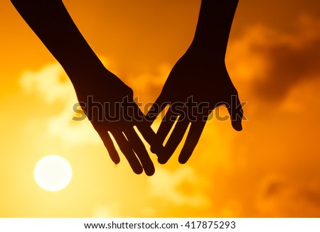 Male and female hands coming together in a beautiful sunset setting. Love and relationship concept.  - stock photo