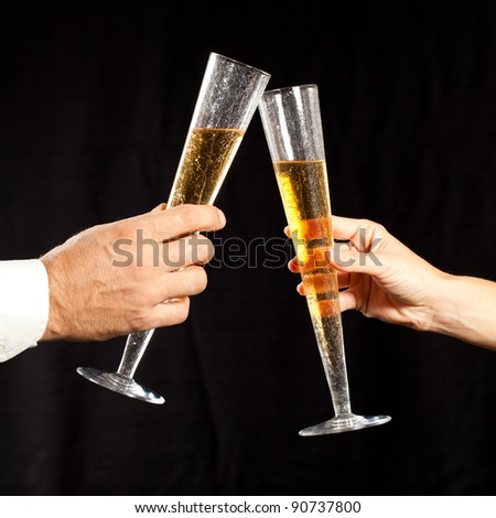 male and female hands holding glass of champagne and tossing against black background - stock photo