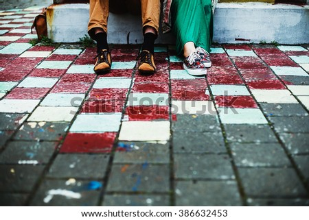Male and female legs and green shoes - stock photo
