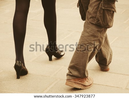 Male and female legs. Closeup. Couple on the bridge over Seine river in Paris. Gender and lifestyle differences concept. Toned photo. - stock photo