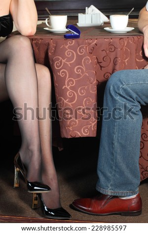 Male and female legs during a date in the restaurant. Closeup of male and female legs during a date. - stock photo