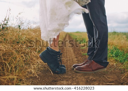 Male and female legs in boots in field. Love,kiss concept.Wedding retro style. - stock photo