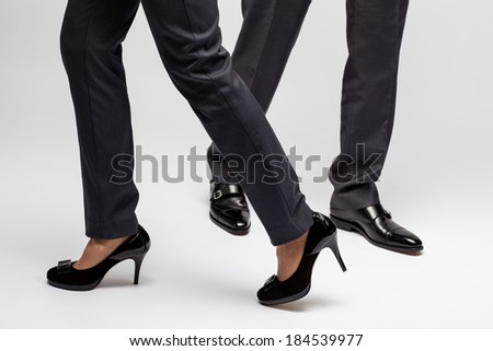 Male and female legs walking on grey background - stock photo