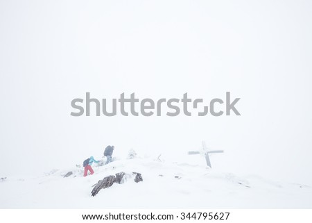 Male and female mountain climbers with backpacks and trekking poles successful finishing their extreme winter hiking trip to top of mountain with cross during blizzard in Austrian Alps - stock photo