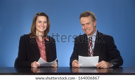 Male and female newscasters sitting at desk smiling at viewer. - stock photo