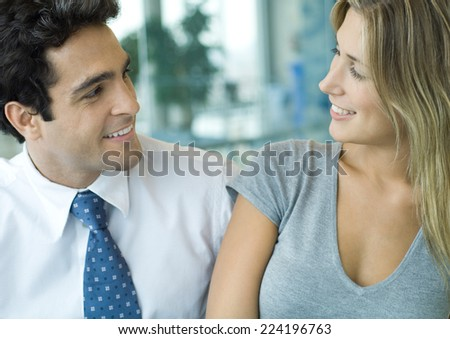 Male and female office workers smiling at each other - stock photo