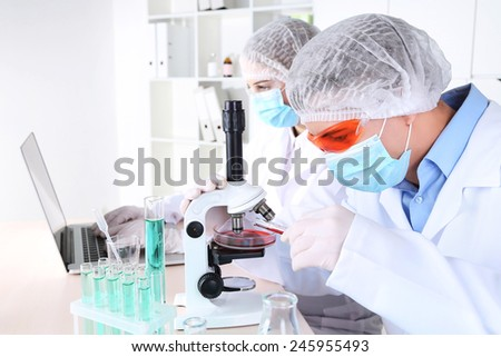 Male and female scientists using microscope in laboratory - stock photo