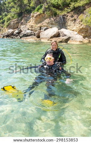 Male and female scuba divers have fun during a recue diver course - stock photo