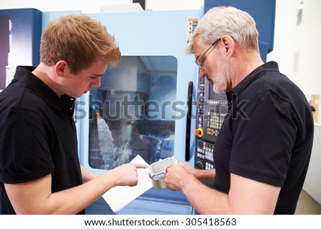 Male Apprentice Working With Engineer On CNC Machinery - stock photo