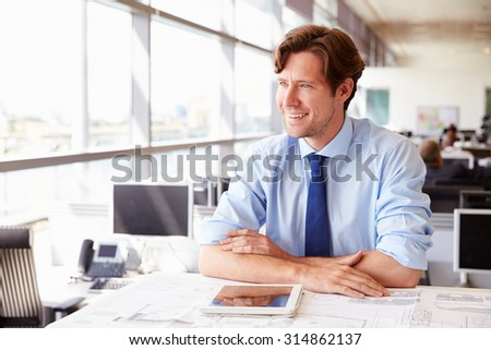 Male architect at his desk in an office, looking away - stock photo