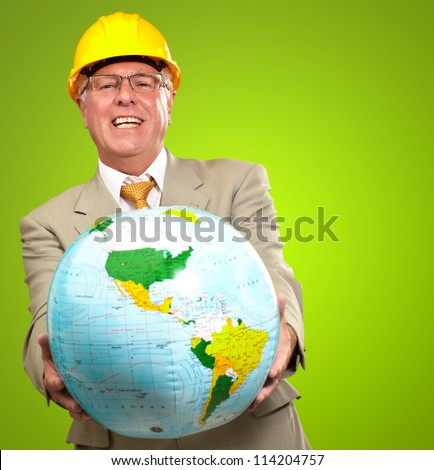 Male Architect Pointing At Globe On Green Background - stock photo