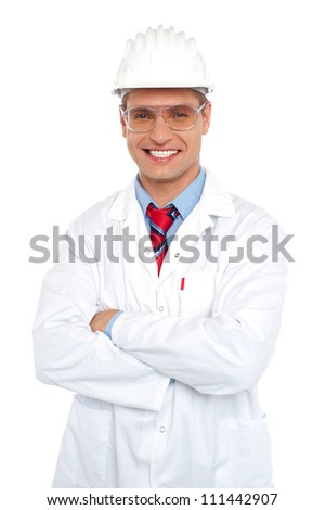 Male architect wearing safety glasses and hard hat. Dressed in white uniform  with arms folded - stock photo