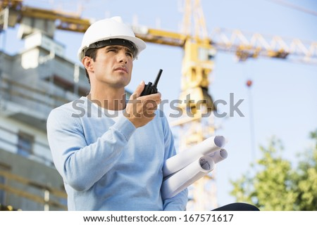 Male architect with blueprints using walkie-talkie at construction site - stock photo