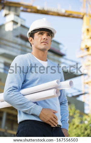 Male architect with rolled up blueprints standing at construction site - stock photo