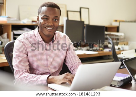 Male Architect Working At Desk On Laptop - stock photo