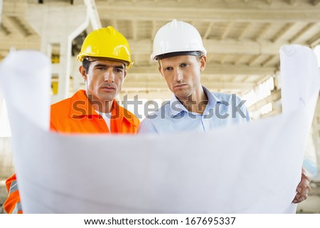 Male architects reviewing blueprint at construction site - stock photo