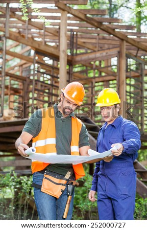 Male architects studying blueprint outside incomplete wooden cabin at construction site - stock photo