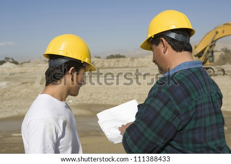 Male architects wearing hard hat at construction site - stock photo