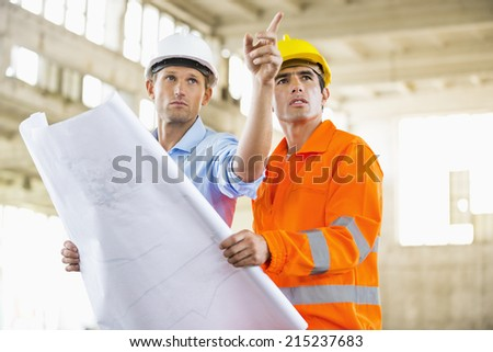 Male architects with blueprint working at construction site - stock photo