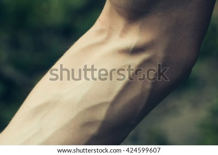 Male arm with visible veins outdoor closeup - stock photo