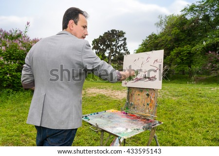 Male artist looking through a park during creation a sketch of his picture on a trestle and easel painting with oils and acrylics in a garden - stock photo