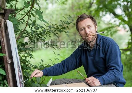 Male artist on painting on canvas in outdoor. Fine art artist. Plein-air. - stock photo