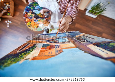 Male artist painting street of Venice on canvas - stock photo