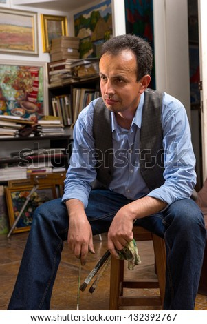 Male artist sitting thinking in a studio with a paint brush and rag in his hand with a dejected expression as though not happy with the result - stock photo