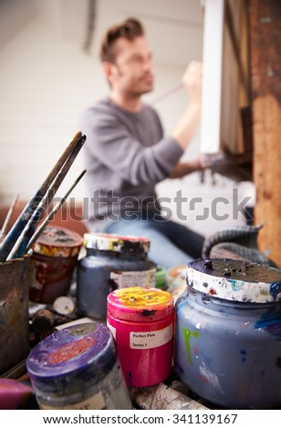 Male Artist Working On Painting In Studio - stock photo
