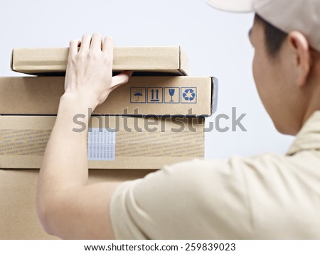 male asian courier company worker checking packages to be delivered. - stock photo