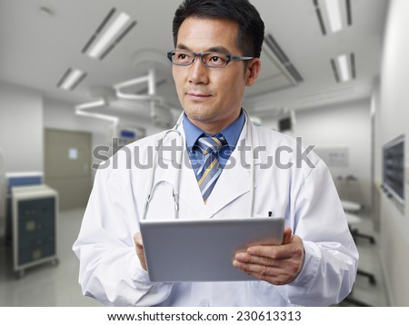 male asian doctor with tablet computer. - stock photo