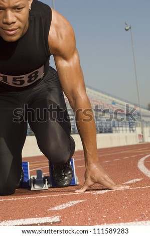 Male athlete at starting line in racetrack - stock photo