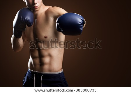 Male Athlete Boxer Punching On Brown Background - stock photo