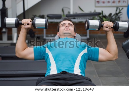 Male athlete doing a dumbbell bench press. - stock photo