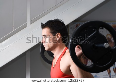 Male athlete doing squats with a barbell. - stock photo
