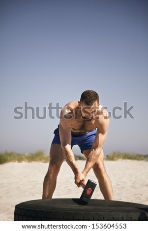 Male athlete hammering truck tire with a sledgehammer during workout on beach - stock photo