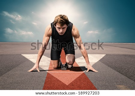Male athlete on airport runway preparing for his start - stock photo