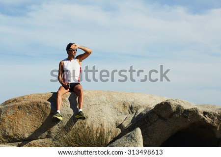 Male athlete resting after an active exercise while sitting on big rock stone,mature sports man enjoying a rest while sitting on the background of cloudy sky with copy space area for your text message - stock photo