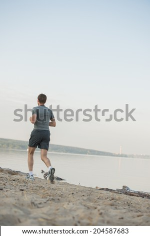 Male athlete/runner running on beach - jog workout well-being concept. Behind view - stock photo