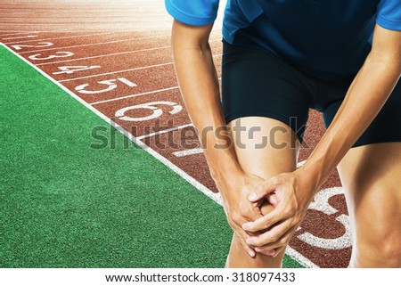 Male athlete runner touching foot in pain due to sprained ankle - stock photo