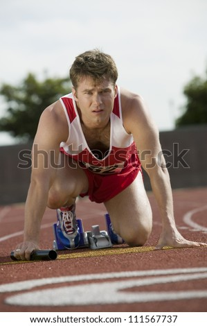 Male athlete with baton preparing for relay race - stock photo