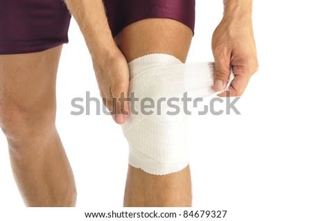 Male athlete wraps knee injury with bandage - stock photo