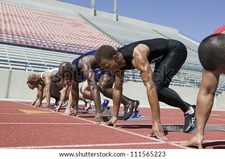Male athletes at starting line in track race - stock photo