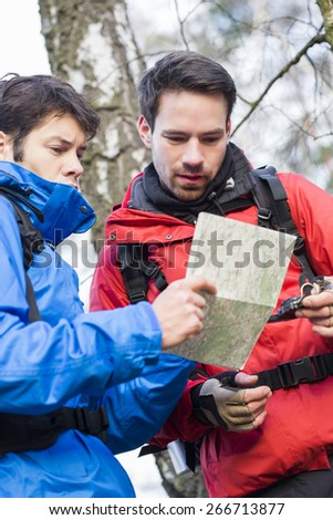Male backpackers reading map together in forest - stock photo