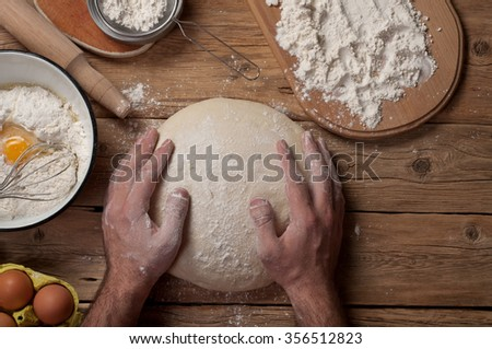 Male baker prepares bread on a wooden table in a bakery closeup. Top view. Copy space - stock photo