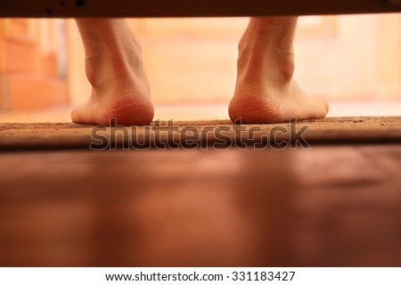 male bare feet photo from under the bed, selective focus - stock photo