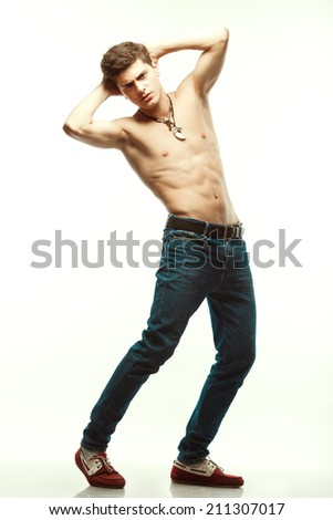 Male beauty & Blue jeans concept. Handsome male model in trendy jeans and red loafers with perfect muscular body posing over white background. Leather accessories. Urban style. Full length portrait - stock photo