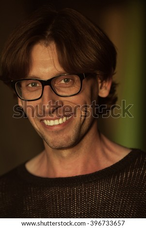 Male beauty concept. Emotional portrait of laughing handsome man in black knitted sweater posing. Glossy long hair, shiny perfect smile. Close up. Trendy eyewear. Indoor shot - stock photo