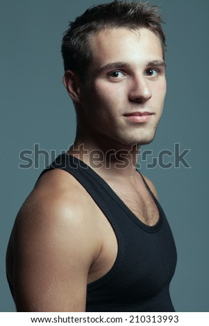 Male beauty concept. Emotive portrait of handsome young man looking at camera in black sleeveless shirt. Great muscles and healthy skin. Urban style. Studio shot - stock photo